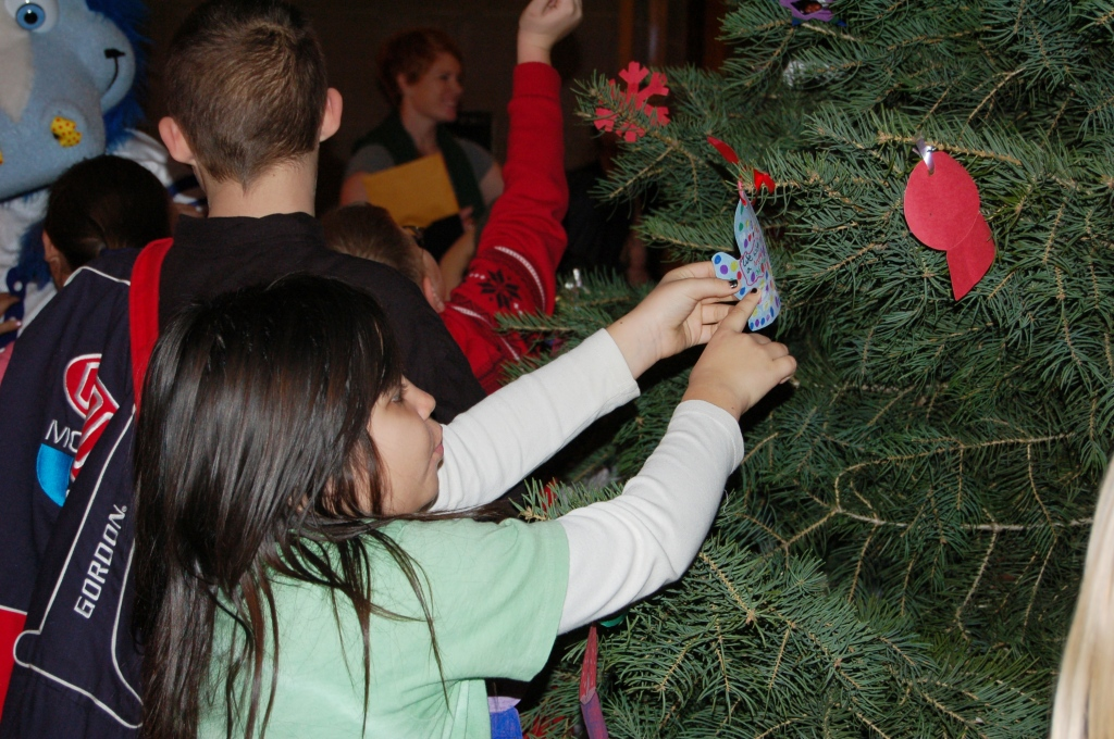 A student decorates the tree with her ornament